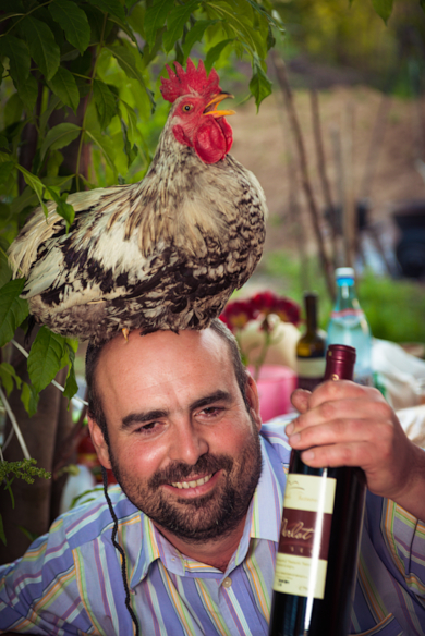 man with rooster on head